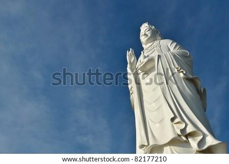 buddha statue on blue sky background, vietnam - stock photo