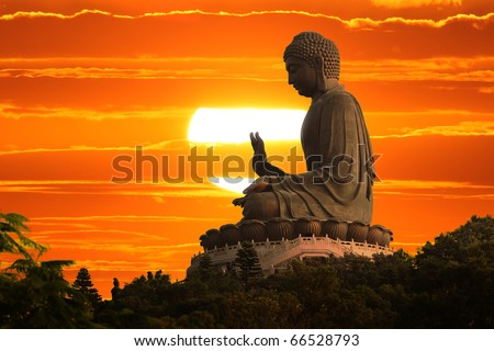 Buddha statue over scenic sunset sky background - stock photo