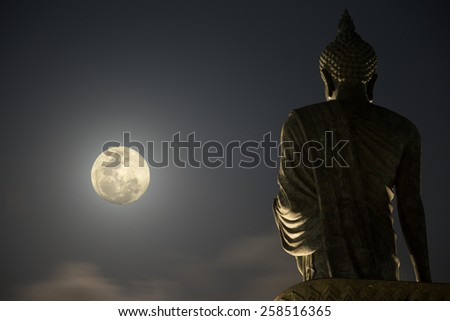Buddha Statue under the moonlight (focused on the statue) - stock photo