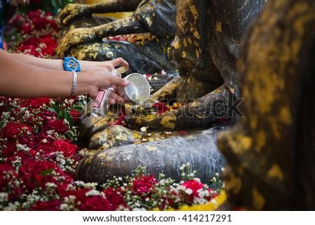 Buddha statue water ceremony in happy new year Thai festival - stock photo