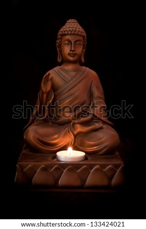 Buddha statue with a candle on a black background - stock photo
