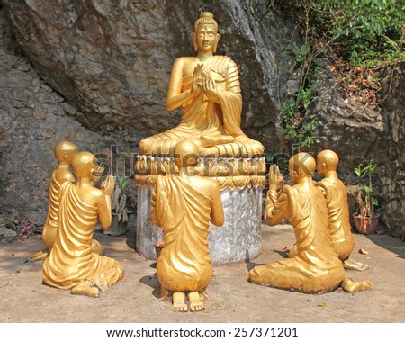 Buddha Statue with monks praying.  Buddhism is an integral part of life in UNESCO listed town of Luang Prabang in Laos - stock photo