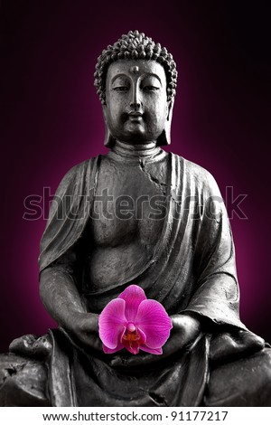 Buddha statue with orchid against black background - stock photo
