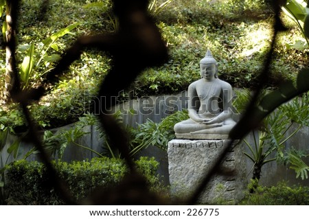 Buddha statue with smaller blurred statue in foreground. - stock photo