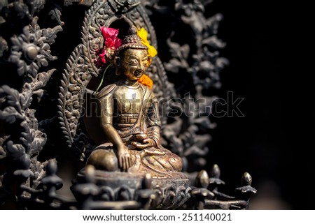 Buddha statue with yellow and red flowers in Patan, Nepal    - stock photo