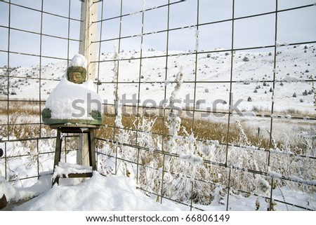 Buddha Statue Wrapped in a Blanket of Snow Against a Fence. - stock photo