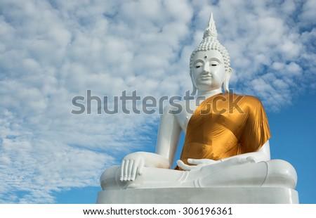 Buddha status on blue sky background - stock photo