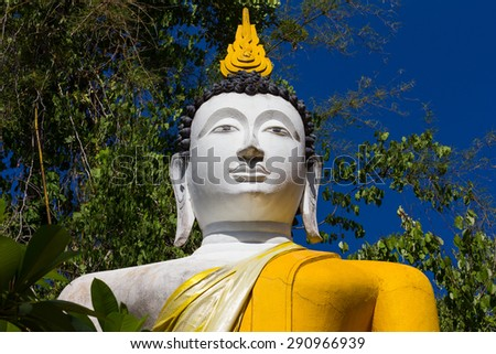 Buddha white stucco yellow blanket hidden in bushes, the leaves of the trees to the sky. - stock photo