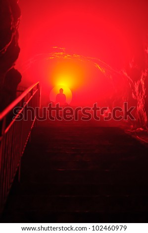 Buddha with red light in cave - stock photo
