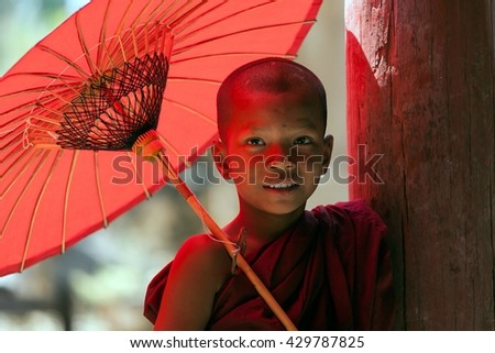 Buddhism novices with umberella in temple  MYANMAR - march 10: Unidentified novice monk with red umbrella in buddhist temple on march 10, 2016 in Mrauk U, Myanmar - stock photo