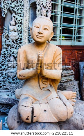 Buddhist monk carved wood image in a souvenir shop in Mandalay, Myanmar - stock photo