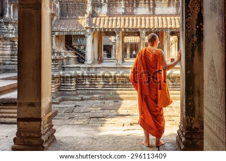 Buddhist monk exploring ancient courtyards of temple complex Angkor Wat in Siem Reap, Cambodia. Mysterious Angkor Wat is a popular destination of tourists and pilgrims. - stock photo