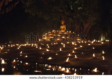 Buddhist monk fire candles to the Buddha with beautiful water reflection in Phan Tao Temple, Chiangmai, Thailand - stock photo