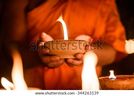 Buddhist monk hands holding candle cup in the dark ,Chiang mai , Thailand - stock photo