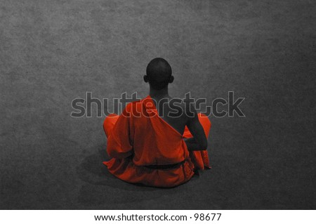 Buddhist monk sitting down in meditation pose - stock photo