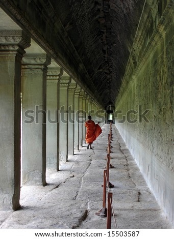 Buddhist monk walking along the longest gallery of Angkor Wat temple, Siem Reap, Cambodia - stock photo