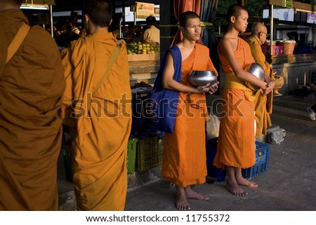 Buddhist monks in prayers and waiting for donation