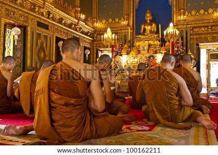 Buddhist monks praying (Thailand) - stock photo