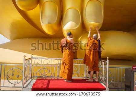 Buddhist monks respect to the hand of big buddha - stock photo