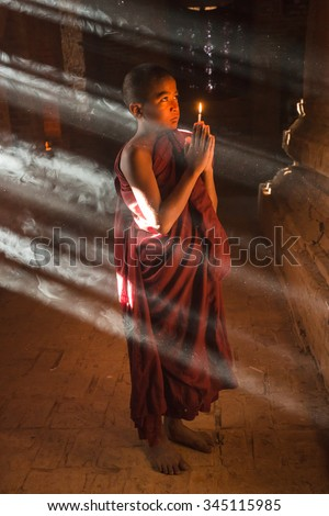 Buddhist novice is praying in temple with sunlight in morning - stock photo