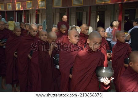 Buddhist novices walk to collect alms and offerings in the monastery of Maha Gandhayon Kyaung ,Mandalay,Myanmar.on 01 December 2013