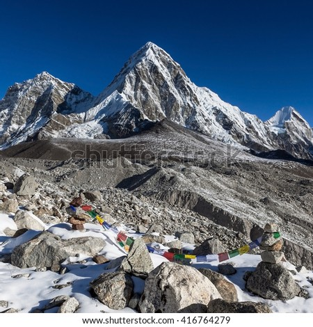 Buddhist prayer flags on mountain cairns on Everest Base Camp route in Himalayas, Nepal. Waving buddhist prayer flags in a beautiful mountain landscape with cairns and Pumori mountain. - stock photo