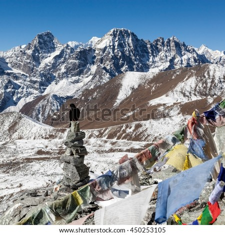 Buddhist prayer flags on mountain cairns on Everest Base Camp route in Himalayas, Nepal. Waving buddhist prayer flags in a beautiful mountain landscape with cairns and black bird sitting on it.