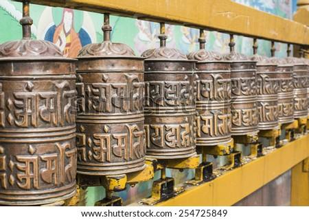 Buddhist prayer wheels with ancient art wall, Nepal - stock photo