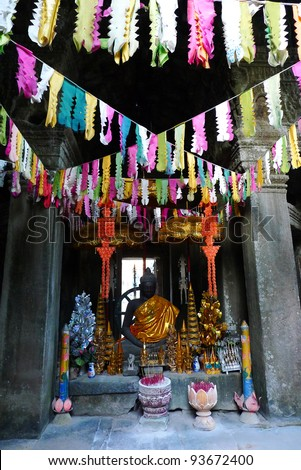 Buddhist shrine with colorful flags at banteay kdei temple, angkor, near siem reap, cambodia - stock photo
