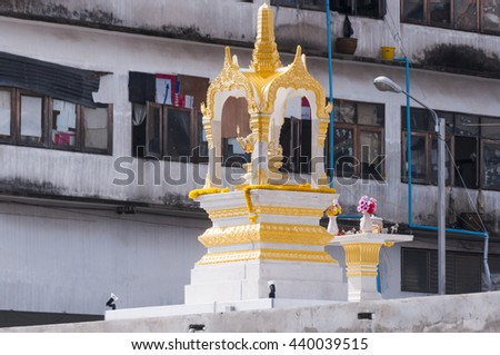 Buddhist spirit house shrine outside Thai home which houses the spiritual guardian of the property Thonburi district in Bangkok - stock photo