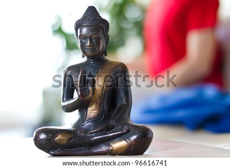 Buddhist statue and person meditating in the background - stock photo