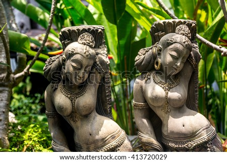 Buddhist statue in stone with a green back ground, Cambodia. - stock photo