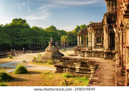 Buddhist Stupa and outer hallway with columns of ancient temple complex Angkor Wat in Siem Reap, Cambodia. Blue sky and woods in background. Mysterious Angkor Wat is a popular tourist attraction.