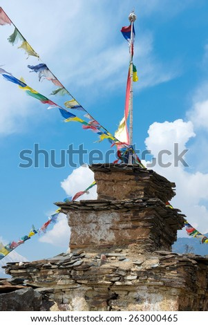 Buddhist stupa with colorful flags on a Annapurna Circuit - most popular tourists trek in Himalayan mountain massive in Nepal. - stock photo