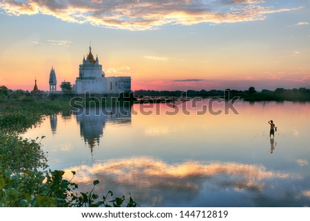 Buddhist temple at sunset reflecting in lake near U bein bridge at Amarapura ,Mandalay, Myanmar.