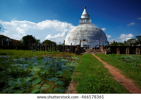 Buddhist Temple, Tissamaharama, Sri Lanka. Path  between two ponds covered in water lilies leading to the white temple, blue sky with clouds in background.