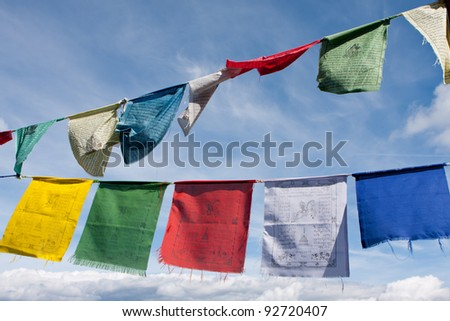 Buddhist tibetan prayer flags flying in the wind against blue sky - stock photo