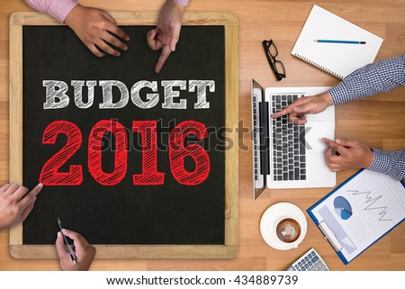 BUDGET 2016 Businessman working at office desk and using computer and objects on the right, coffee,  top view, - stock photo