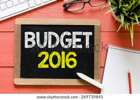 Budget 2016 Handwritten on blackboard. Budget 2016 Handwritten with chalk on blackboard, keyboard,notebook,glasses and green plant on wooden background - stock photo