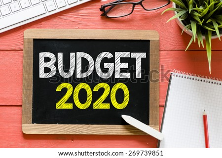 Budget 2020 Handwritten on blackboard. Budget 2020 Handwritten with chalk on blackboard, keyboard,notebook,glasses and green plant on wooden background - stock photo