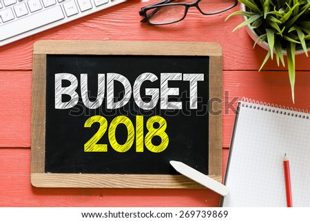 Budget 2018 Handwritten on blackboard. Budget 2018 Handwritten with chalk on blackboard, keyboard,notebook,glasses and green plant on wooden background - stock photo