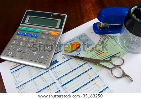 Budget spreadsheet with calculator, scissors, stapler, and paper clips on a wooden desk - stock photo