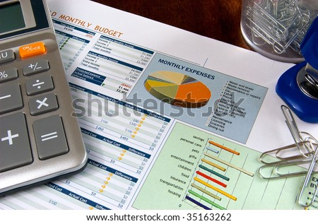 Budget spreadsheet with calculator, stapler, and paper clips on a wooden desk - stock photo