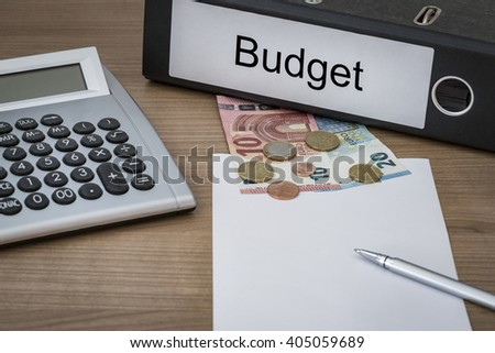 Budget written on a binder on a desk with euro money calculator blank sheet and pen - stock photo