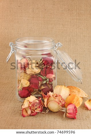 Buds of dry roses in glass bottle on jute background - stock photo