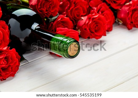 Buds of red roses and bottle of wine on white wooden background