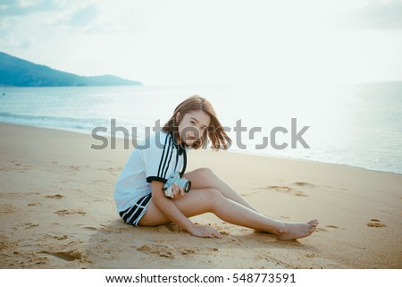 Bueatiful girl holdding camera and sitting on the beach.