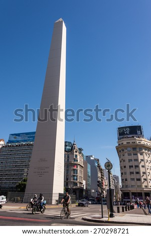 Buenos Aires, Argentina - April 9, 2015: Unidentified business people driving down the street at iconic building  Obelisco on April 9, 2015 in Buenos Aires, Argentina - stock photo