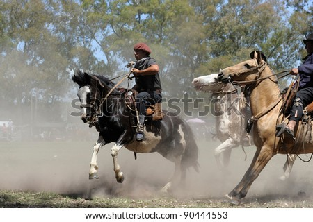 BUENOS AIRES, ARGENTINA - DEC 4: A Gaucho riding an untamed horse in Gaucho National Day Festival. DEC 4, 2011 in Buenos Aires, Argentina - stock photo