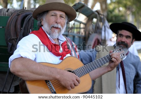 BUENOS AIRES, ARGENTINA - DEC 4: Gauchos playing guitar and singin traditional songs in Gaucho National Day Festival. Dec 4, 2011 in Buenos Aires, Argentina - stock photo